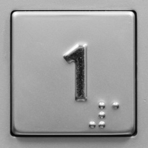 Image of an elevator button with the number 1 and the braile equivalent