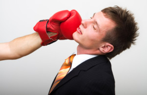 Businessman Being Hit with Boxing Glove