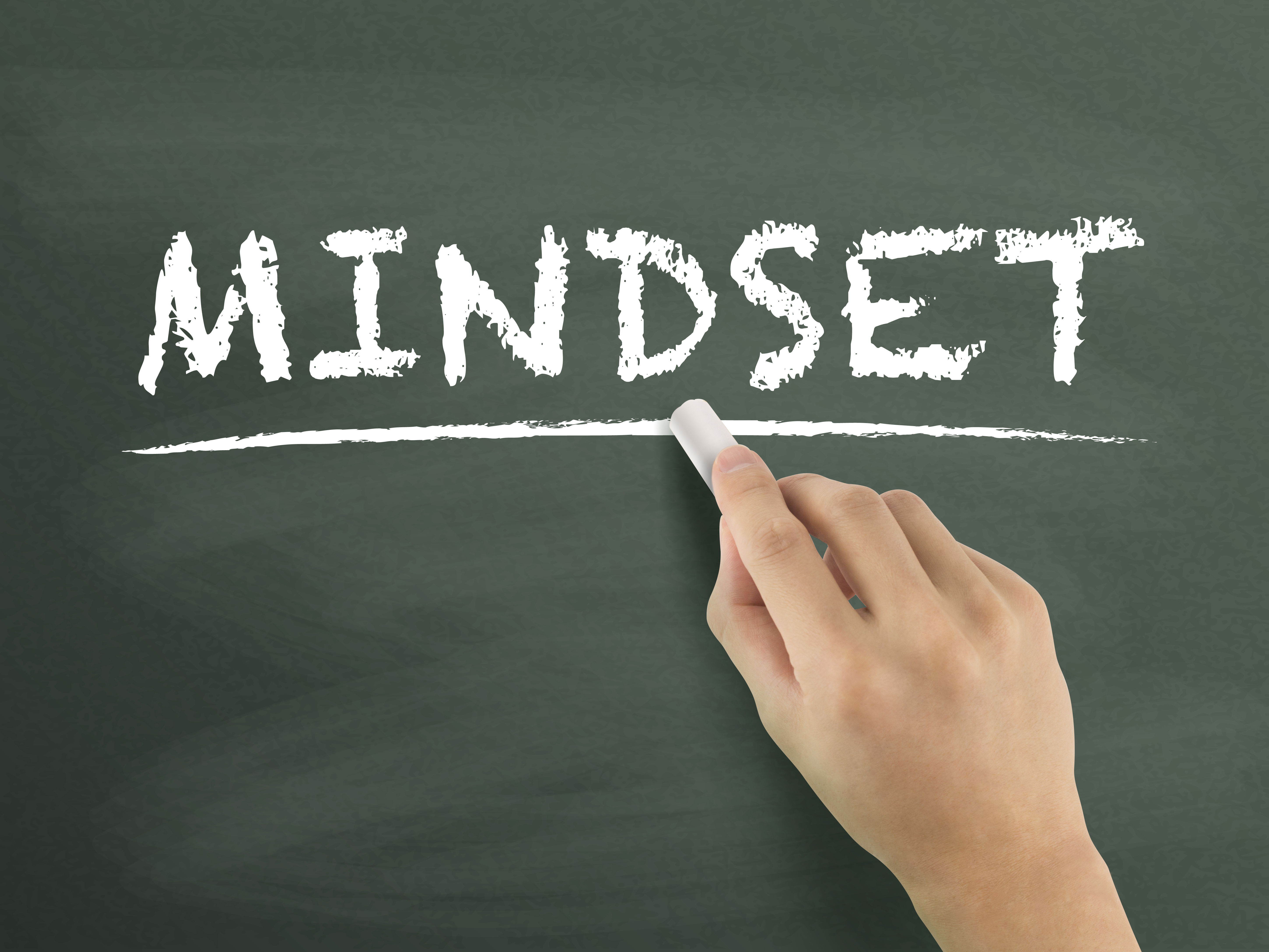 Chalkboard with a person writing the word mindset
