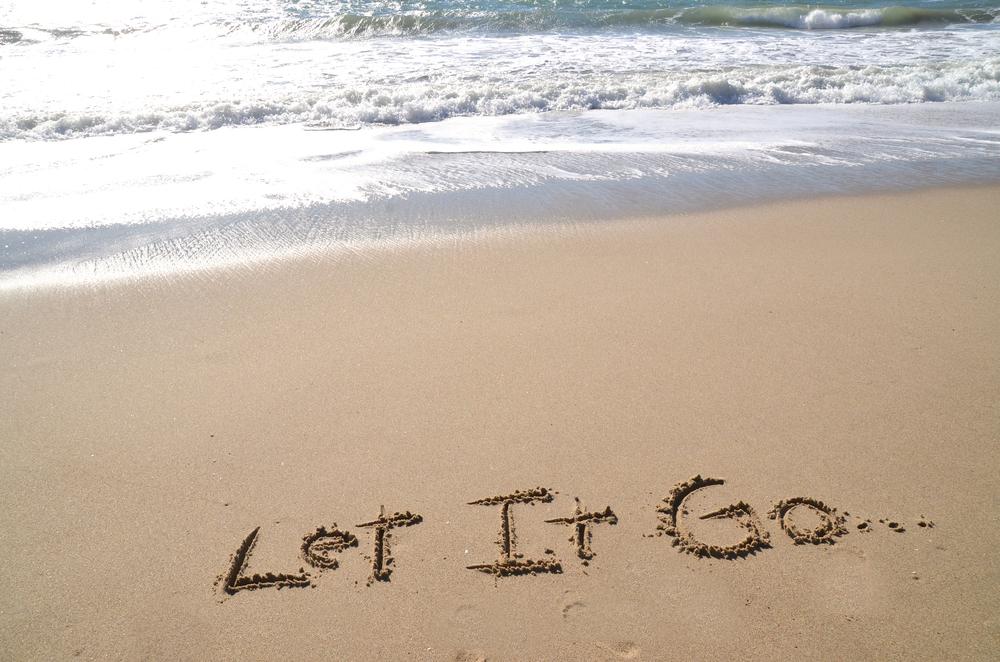 """Words """"Let it Go"""" written in sand"""