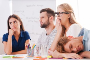 Image of professionals yawning and bored in a meeting