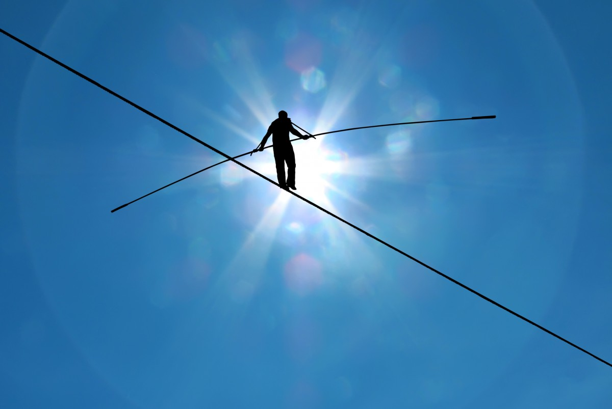 Man walking on a tightrope shown against a blue sky